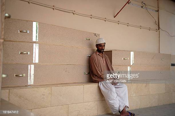 A Pakistani man mourns as he waits in the EDHI Morgue to identify his relative who was killed in a garment factory fire in Karachi on September 13...