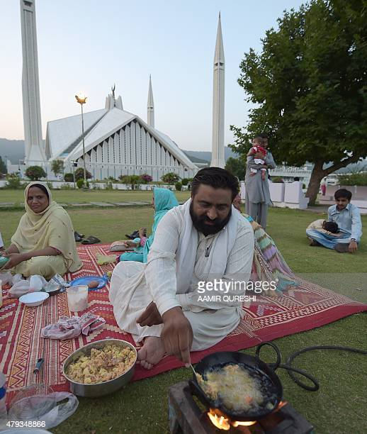 A Pakistani man prepares Iftar food for his family to break their Ramadan fast beside the grand Faisal Mosque in Islamabad on July 3 2015 Ramadan is...