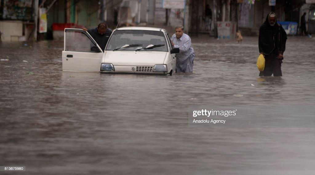 Pakistani man pushes a car through a flooded street after heavy monsoon rains hit Rawalpindi province of Pakistan on July 13 2017 Heavy monsoon rains.