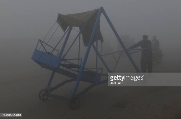 A Pakistani man pushes his swing on a road amid heavy fog and smog conditions in Lahore on January 17 2019 Smog levels spike during winter in...