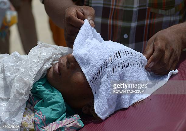 A Pakistani man puts wet towel on the head of a heatstroke victim at a hospital in Karachi on June 30 2015 Nearly twothirds of the victims of a...