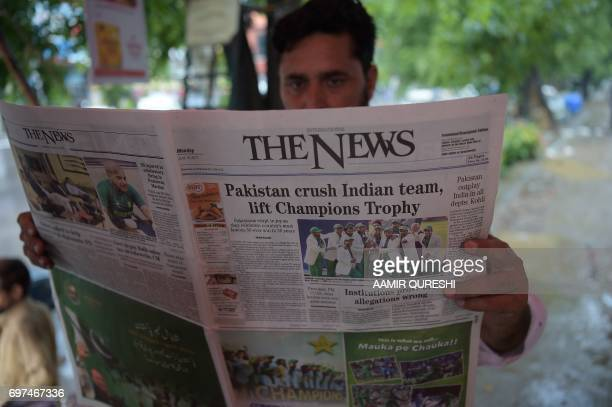 A Pakistani man reads a morning newspaper with front page coverage of Pakistan's victory against India in the ICC Champions Trophy final cricket...