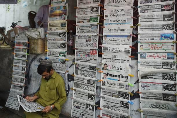 A Pakistani man reads a newspaper at a newstand displaying
