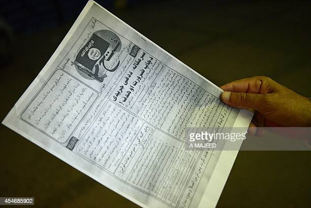 A Pakistani man reads a pamphlet allegedly distributed by the Islamic State in the northwestern Pakistani city of Peshawar on September 5 2014 The...