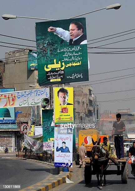 A Pakistani man rides a horsedrawn cart past banners and placards of Pakistani politicians on a street in Lahore on October 27 2011 Tens of thousands...
