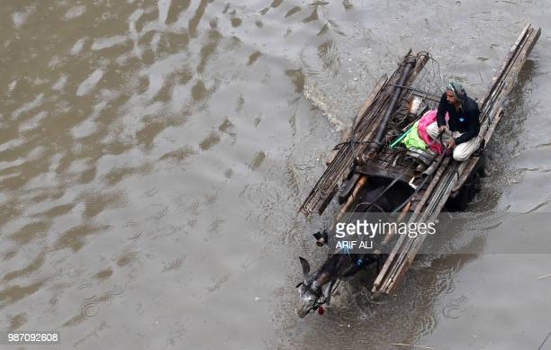 Pakistani man rides on a donkey cart through a flooded street after heavy rains in Lahore on June 29 2018