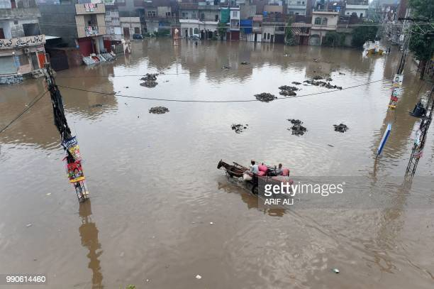 Pakistani man rides on his horse cart through a flooded square after heavy rains in Lahore on July 3 2018