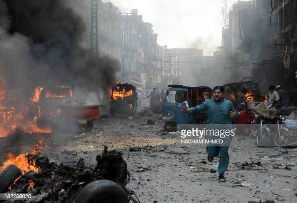 A Pakistani man runs past burning vehicles at the site of a bomb explosion in the busy Kissa Khwani market in Peshawar on September 29 2013 A bomb...