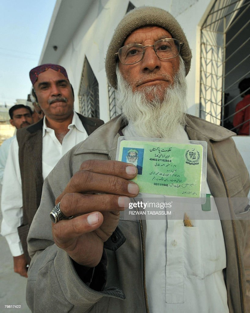 A Pakistani man shows his identity card prior to casting his