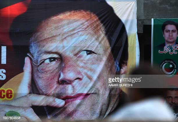 Pakistani man sits near a poster of Pakistan's cricketer-turned politician and head of the Pakistan Tehreek-e-Insaf party Imran Khan, in Islamabad on...