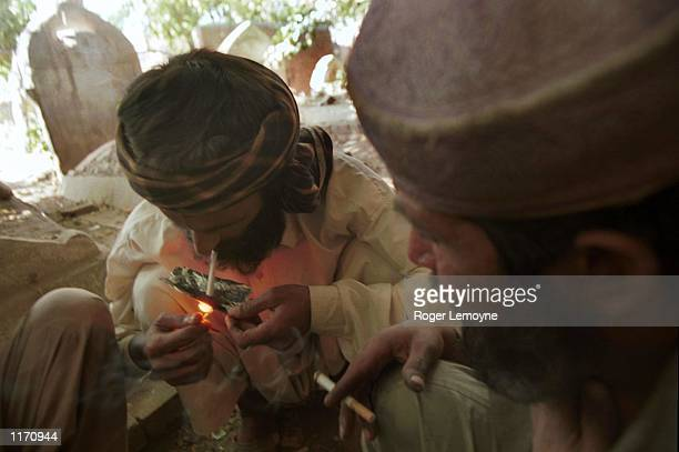 Pakistani man smokes heroin in a graveyard in October 15 2001 in Peshawar Pakistan near the border of Afghanistan The men say that the police are...