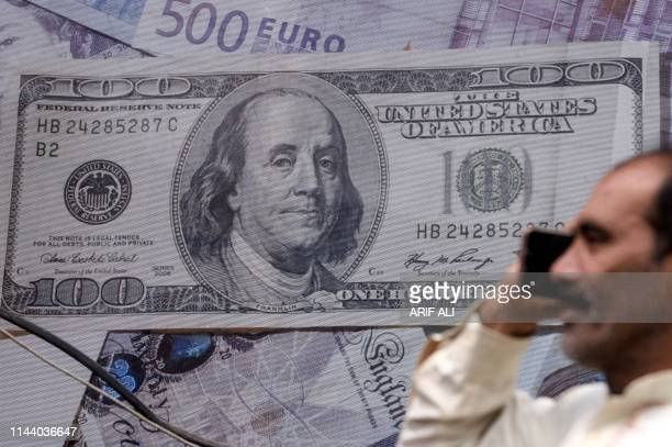 A Pakistani man talks on the phone in front of a poster displaying US dollars at the currency exchange place in Lahore on May 16 2019 Pakistan's...