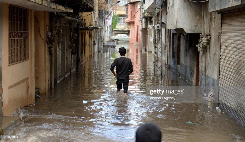 Pakistani man tries to pass through a flooded street after heavy monsoon rains hit Rawalpindi province of Pakistan on July 13 2017 Heavy monsoon...