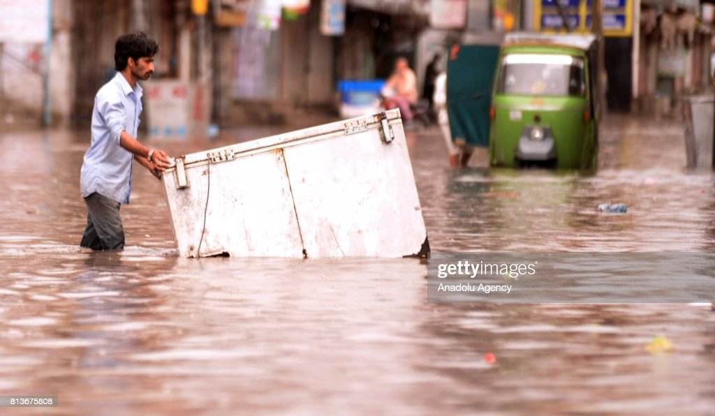 Pakistani man tries to pass through a flooded street with a fridge after heavy monsoon rains hit Rawalpindi province of Pakistan on July 13 2017...