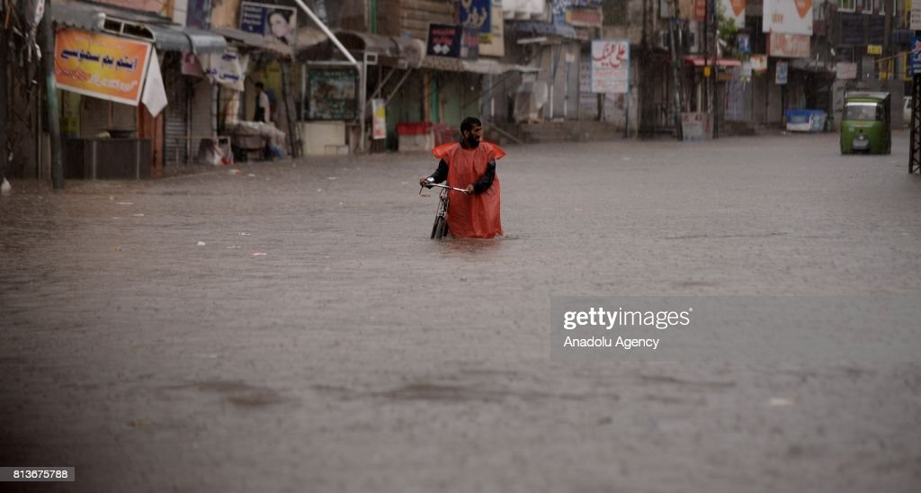 Pakistani man tries to pass through a flooded street with his bike after heavy monsoon rains hit Rawalpindi province of Pakistan on July 13 2017...