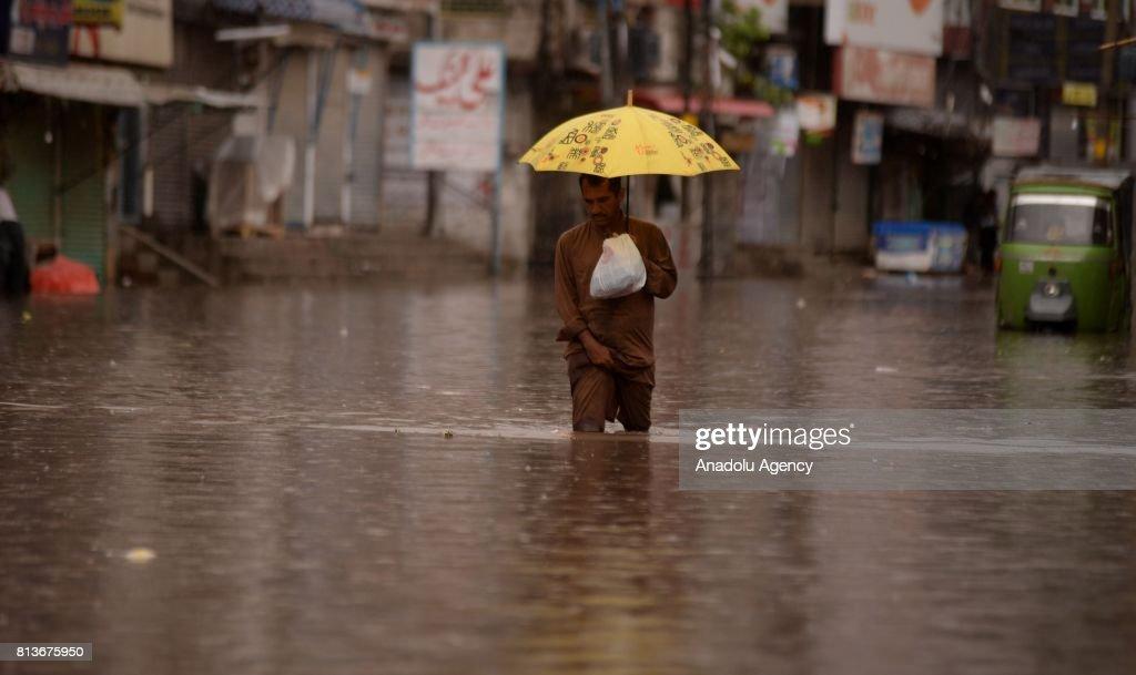 Pakistani man wades through a flooded street after heavy monsoon rains hit Rawalpindi province of Pakistan on July 13 2017 Heavy monsoon rains...
