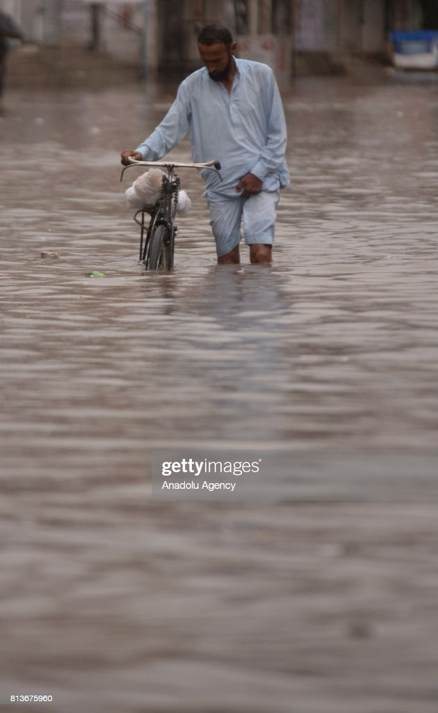 Pakistani man wades through a flooded street with his bike after heavy monsoon rains hit Rawalpindi province of Pakistan on July 13 2017 Heavy...