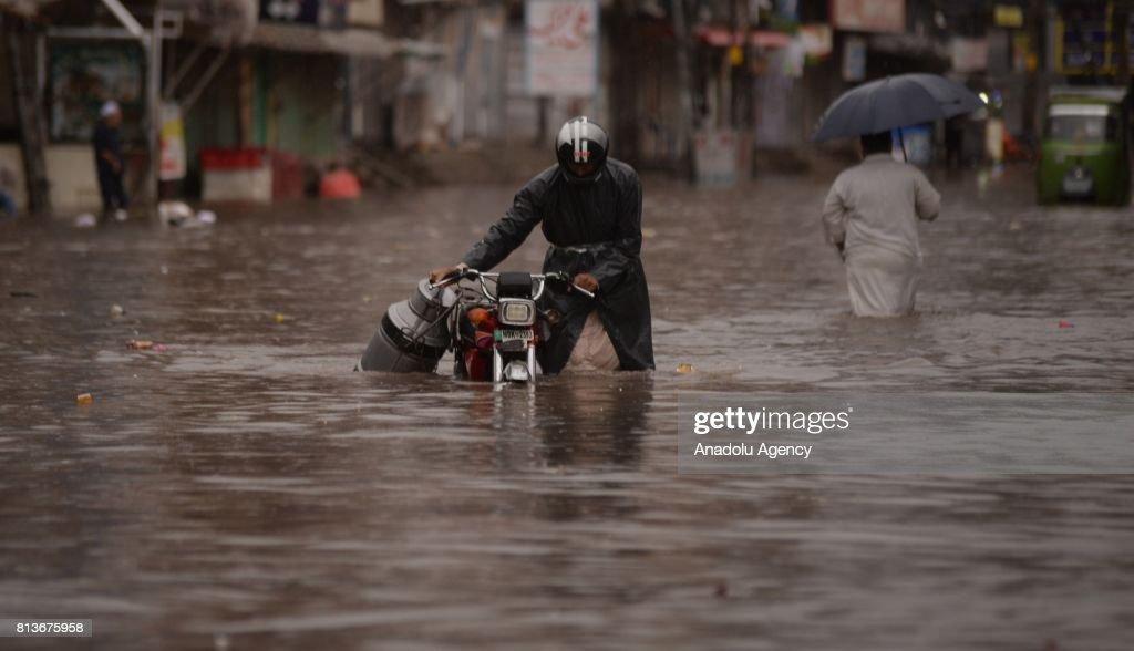 Pakistani man wades through a flooded street with his motorbike after heavy monsoon rains hit Rawalpindi province of Pakistan on July 13 2017 Heavy...