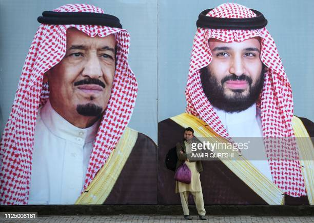 Pakistani man waits for transport in front of billboards showing portraits of Saudi Arabian Crown Prince Mohammed bin Salman and his father and Saudi...