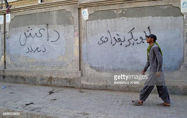A Pakistani man walks past a wall graffiti reading 'Abu Bakr alBaghdadi' leader of the Islamic State jihadist group in Iraq in Quetta on November 24...