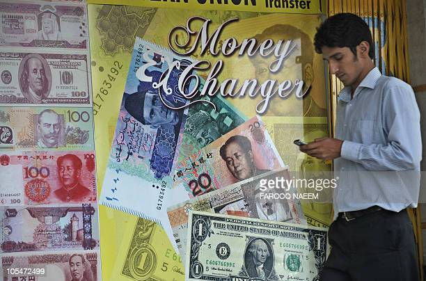 A Pakistani man walks past an currency exchange shop in Islamabad on October 14 2010 The US dollar fell against most Asian currencies while the...