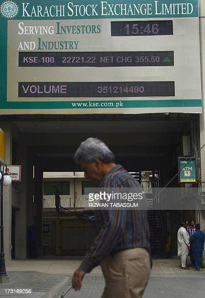 A Pakistani man walks past an index board outside the Karachi Stock Exchange in Karachi on July 9 2013 The benchmark KSE100 index closed at 2272122...