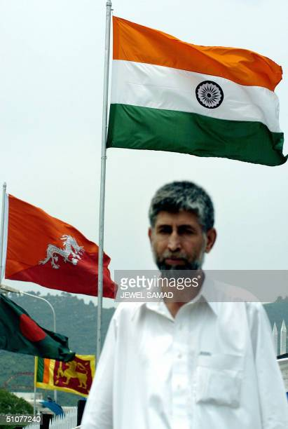 Pakistani man walks past as the Indian flag flutters in the wind along with other country flags of the South Asian Association for Regional...