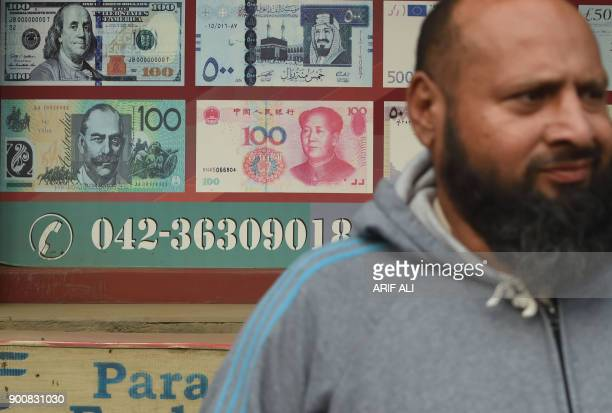 A Pakistani man walks past the currency exchange shop in Lahore on January 3 2018 Pakistan will allow the Chinese yuan to be used for imports exports...