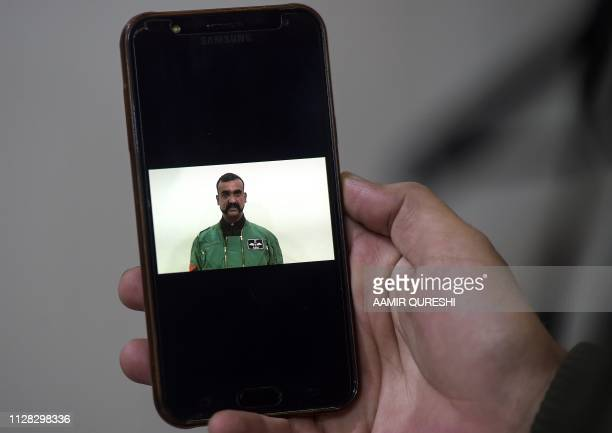 A Pakistani man watches the latest video statement released by Pakistan's military authorities of the Indian Wing Commander pilot Abhinandan...