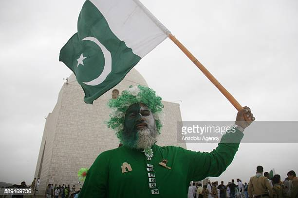 Pakistani man with his face painted in national colors holds a Pakistani flag during a ceremony marking Pakistan's 69th Independence Day at the...
