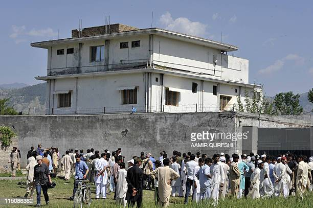 Pakistani media personnel and local residents gather outside the hideout of AlQaeda leader Osama bin Laden following his death by US Special Forces...