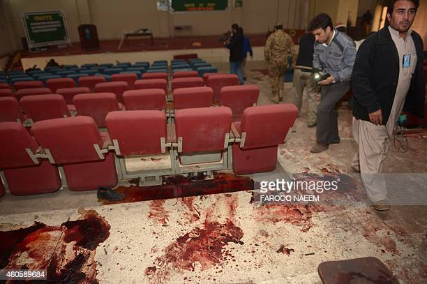 Pakistani media walk in the bloodied ceremony hall at an armyrun school a day after an attack by Taliban militants in Peshawar on December 17 2014...