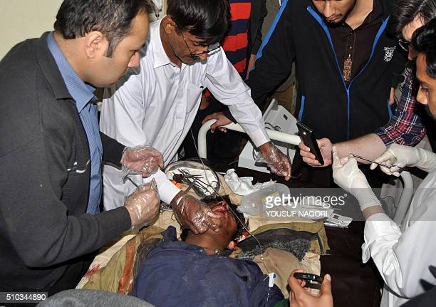 Pakistani medical personnel attend to a victim of an overnight accident where a train collided with a minivan in Allah Dino Sand near Hyderabad on...