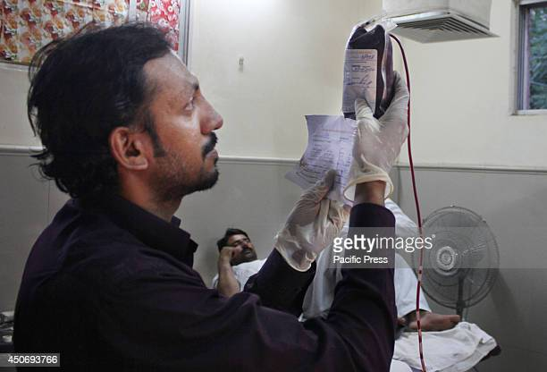 Pakistani medical technologist examines the donated blood at Mayo Hospital during the World Blood Donors Day