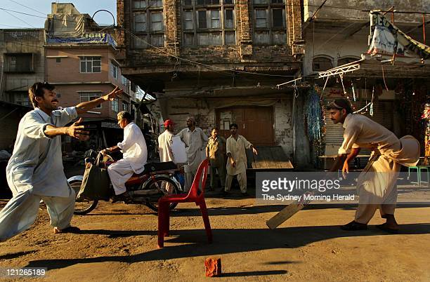 Pakistani men and boys play tape-ball cricket in the streets of Rawalpindi on August 9, 2011 in Rawalpindi, Pakistan. Although test cricket has been...