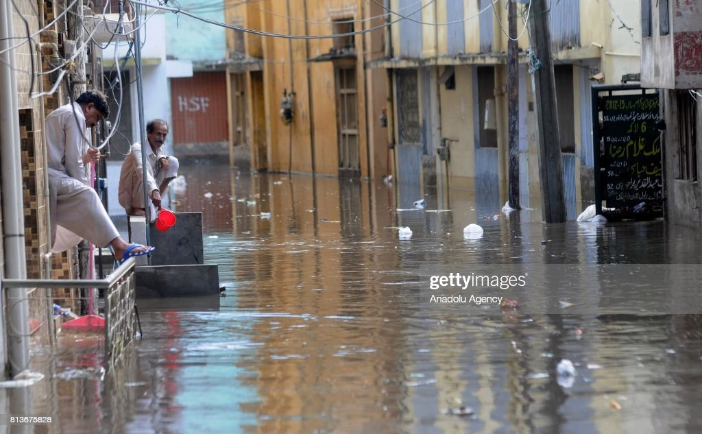 Pakistani men are seen in front of their houses during a flood after heavy monsoon rains hit Rawalpindi province of Pakistan on July 13 2017 Heavy...