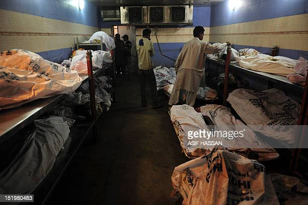 Pakistani men attempt to identify their relatives who died in a garment factory fire at the EDHI Morgue in Karachi on September 14 2012 Three...