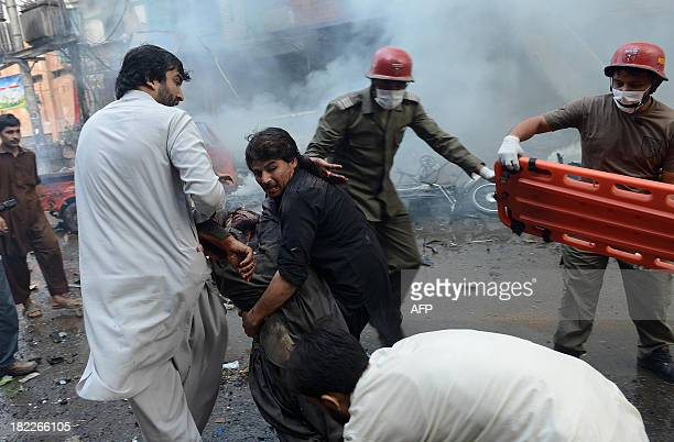 Pakistani men carry an injured blast victim at the site of a bomb explosion in the busy Kissa Khwani market in Peshawar on September 29 2013 A bomb...