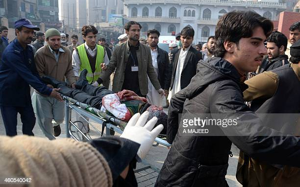 Pakistani men carry an injured student to a hospital following an attack by Taliban gunmen on a school in Peshawar on December 16 2014 At least 130...
