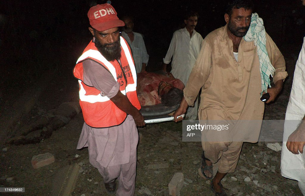 Pakistani men carry the body of a blast victim at the site of suicide car bombing in the southern city of Sukkur on July 24, 2013. Suicide car bombers and gunmen attacked a government complex housing offices of Pakistan's top intelligence agency, sparking a shootout that killed seven people, officials said.