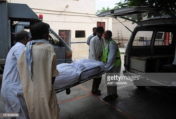 Pakistani men carry the coffin of their relative who died in a garment factory fire from the EDHI Morgue in Karachi on September 13 2012 More than...