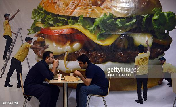 Pakistani men eat burgers at a mall in Islamabad on October 25 2014 AFP PHOTO/ Aamir QURESHI