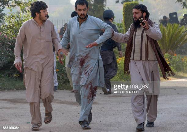 Pakistani men help an injured after rescued from an Agriculture Training Institute after an attack by Taliban militants in Peshawar on December 1...