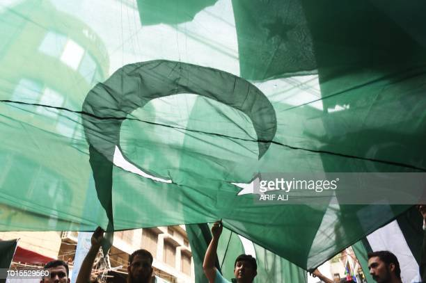 TOPSHOT Pakistani men hold a national flag in a stall ahead of the upcoming Independence Day celebrations in Lahore on August 12 2018 Pakistan will...