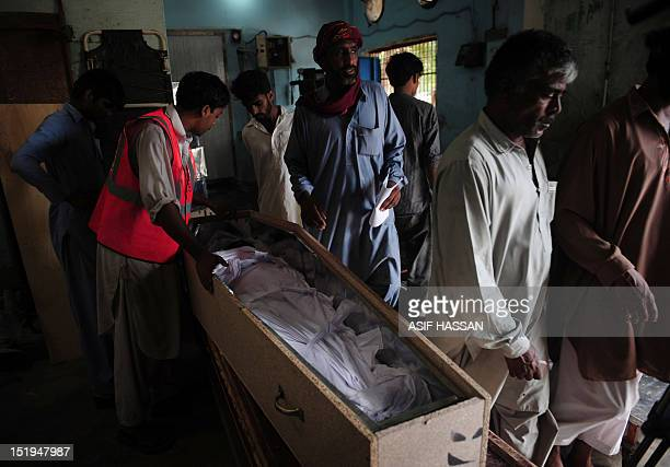 Pakistani men identify their relatives who died in a garment factory fire at the EDHI Morgue in Karachi on September 13 2012 More than 310 Pakistanis...