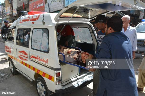 Pakistani men lift an injured shopkeeper in an ambulance after assailants opened fire at an electronics shop in Quetta on April 28 2018 Two people...