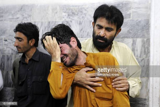 Pakistani men mourn the death of a police officer at a hospital in Quetta on September 7 2012 Motorbike gunmen Friday shot dead a senior police...