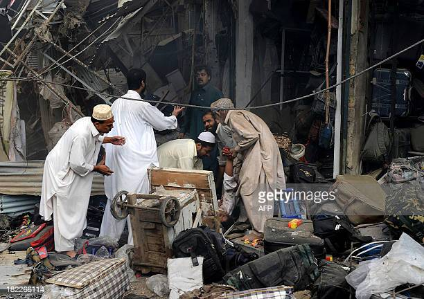 Pakistani men move the body of a blast victim at the site of a bomb explosion in the busy Kissa Khwani market in Peshawar on September 29 2013 A bomb...