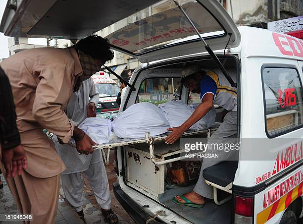 Pakistani men move the body of their relative who died in a garment factory fire into an ambulance from the EDHI Morgue in Karachi on September 13...