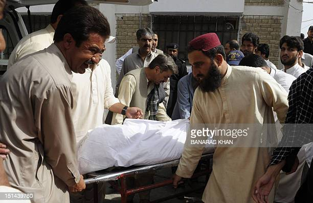Pakistani men move the dead body of police officer in an ambulance outside a hospital in Quetta on September 7 2012 Motorbike gunmen Friday shot dead...